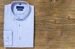 在木背景的蓝色偶然衬衣 免版税库存照片