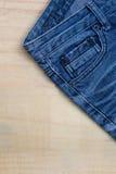 在木背景的蓝色牛仔裤设计 库存照片
