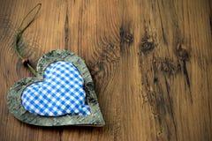 在木背景的蓝色白色方格的心脏枕头与拷贝 免版税图库摄影