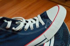 在木背景的蓝色运动鞋 库存图片