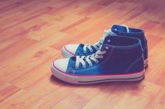 在木背景的蓝色运动鞋 免版税库存图片