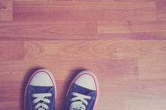 在木背景的蓝色运动鞋 图库摄影