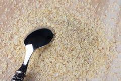 在木背景的被击碎的发芽的麦子种子与金属匙子 免版税库存照片
