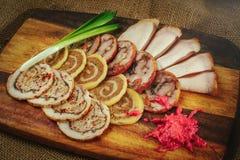 在木背景的被切的可口肉卷用辣根和葱,一次舒适餐馆服务,桌设置 库存照片