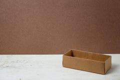在木背景的被打开的纸板箱 免版税库存照片