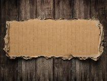 在木背景的被撕毁的纸板 免版税库存照片