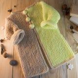 在木背景的被编织的毛线衣 免版税库存图片