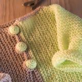 在木背景的被编织的毛线衣 免版税库存照片