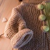 在木背景的被编织的毛线衣 图库摄影