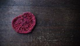 在木背景的被编织的红色心脏 库存照片