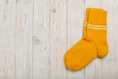 在木背景的被编织的羊毛袜子黄灯 免版税图库摄影