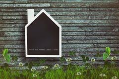 在木背景的议院形状的黑板 免版税库存图片
