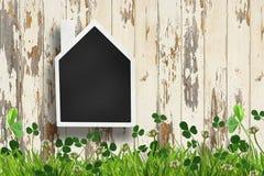 在木背景的议院形状的黑板 免版税库存照片