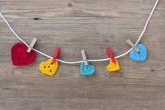 在木背景的许多多色钩针编织心脏为情人节 库存图片