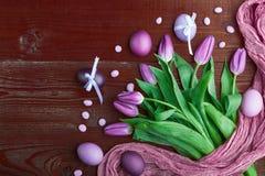 在木背景的豪华新鲜的时兴的紫色郁金香在复活节彩蛋旁边 库存照片