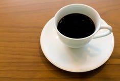 在木背景的软的焦点无奶咖啡杯 免版税库存照片