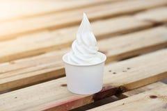在木背景的软的白色奶油色牛奶冰淇凌 库存照片
