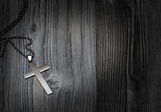 在木背景的金属十字架 图库摄影