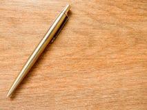 在木背景的金属笔 免版税库存照片
