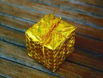 在木背景的金银铜合金礼物 圣诞节在包裹与金螺纹弓的叶子的礼物盒 免版税库存照片