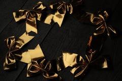 在木背景的金黄圣诞节弓 假日奇迹很快开始 免版税库存图片