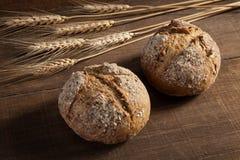 在木背景的面包和麦子耳朵 免版税库存照片