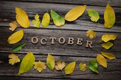 在木背景的题字10月,黄色叶子框架  免版税库存照片