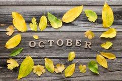 在木背景的题字10月,黄色叶子框架  免版税库存图片