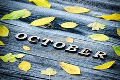 在木背景的题字10月,黄色叶子框架  库存图片