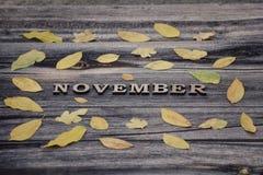 在木背景的题字11月,黄色地方教育局框架  库存图片