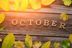在木背景的题字10月,黄色leav框架  免版税库存照片
