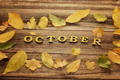 在木背景的题字10月,黄色leav框架  库存照片
