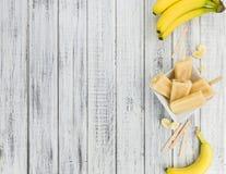 在木背景的香蕉冰棍儿 库存图片