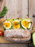 在木背景的鲕梨和蛋三明治 免版税图库摄影