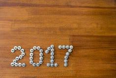 在木背景的2017个新年螺丝 免版税库存图片
