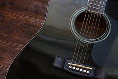 在木背景的黑声学吉他 免版税库存图片