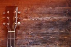 在木背景的黑声学吉他 图库摄影