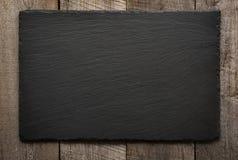 在木背景的黑板岩瓦片 顶视图 免版税库存图片