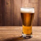在木背景的玻璃啤酒与copyspace 库存照片