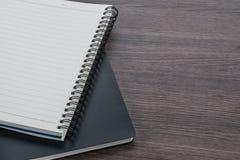 在木背景的黑白笔记本堆 免版税库存图片