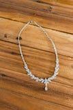 在木背景的钻石项链 免版税图库摄影