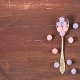 在木背景的紫色和桃红色糖果 库存图片