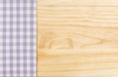 在木背景的紫色方格的桌布 免版税库存图片