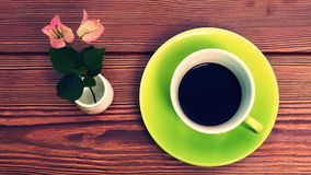 在木背景的绿色杯子咖啡 库存图片