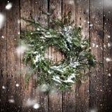 在木背景的绿色自然花圈与落的雪 库存照片