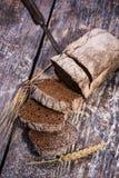 在木背景的黑面包 库存图片