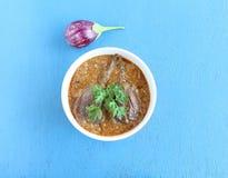 在木背景的Brinjal或茄子印地安素食咖喱 免版税库存图片