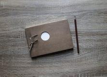 在木背景说谎在笔记薄白色圈子框架的一支工艺笔记薄scrapbooking的铅笔 免版税库存图片