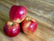 在木背景隔绝的三个红色苹果 免版税库存照片