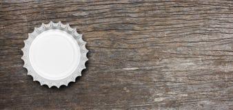 在木背景隔绝的玻璃啤酒瓶盖帽,顶视图,横幅 3d例证 免版税库存照片